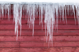 Long thick icicle  hang down of  the roof of a red barn in winter.